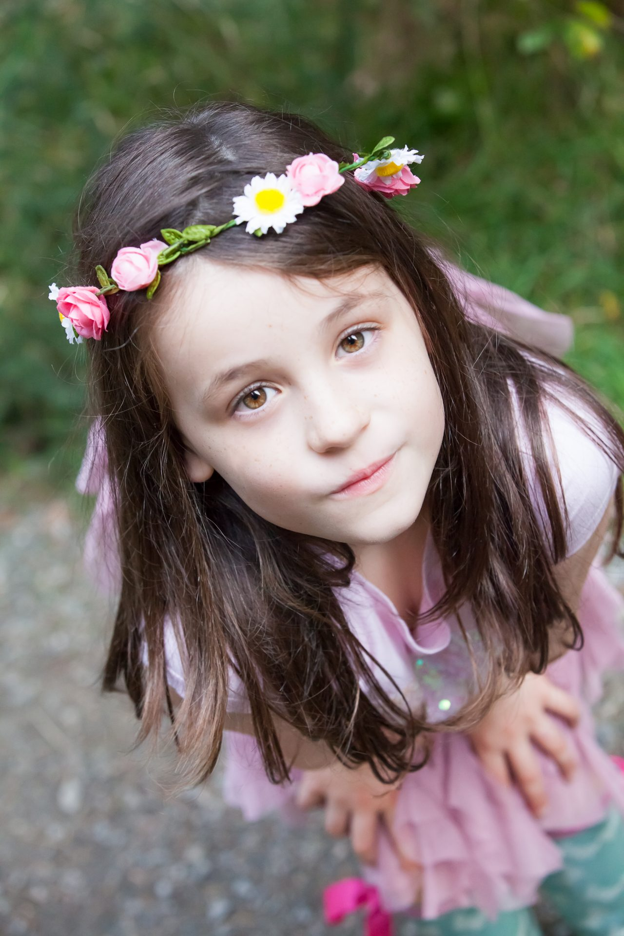young girl with flowers in hair staring up