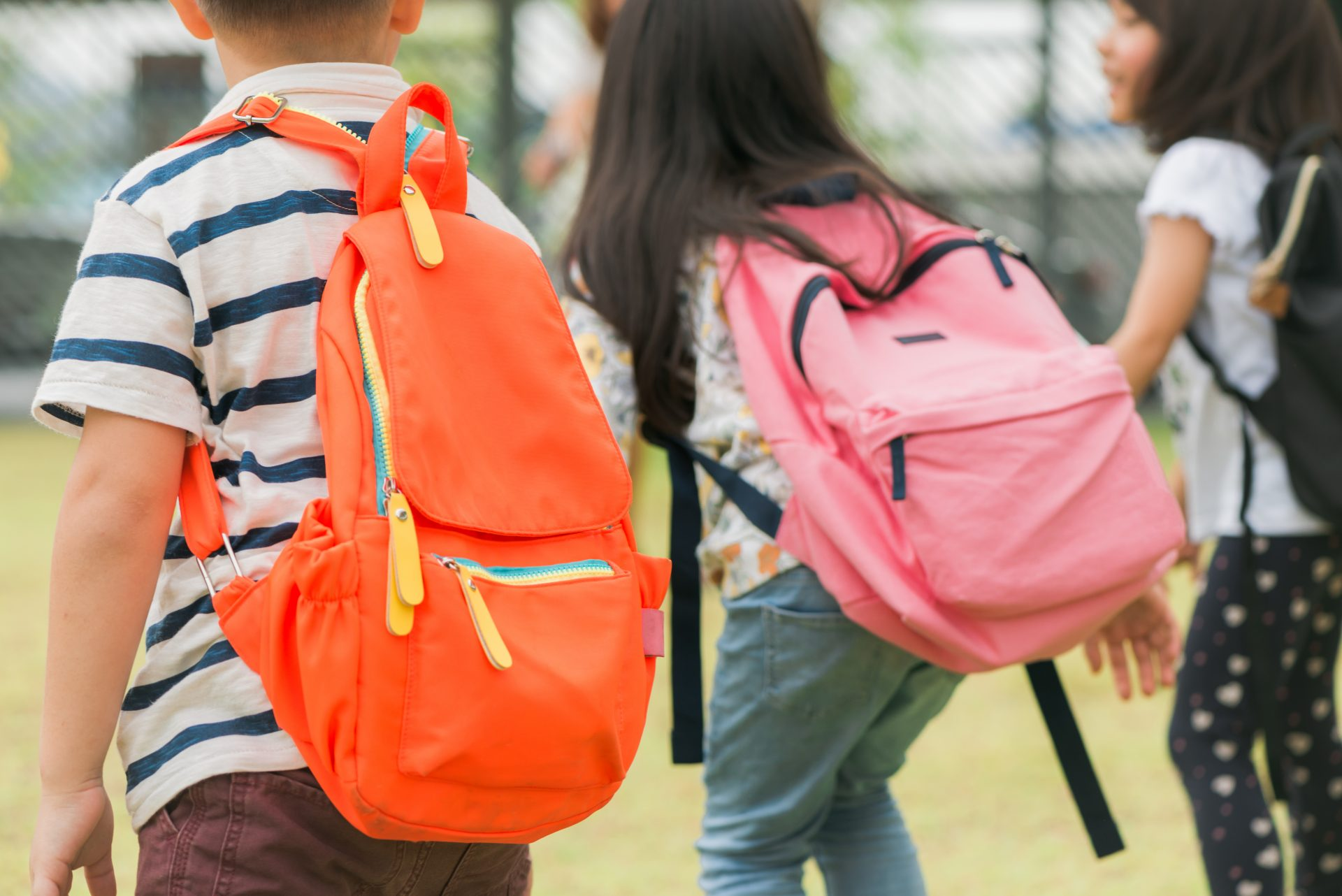 young children walking with backpacks